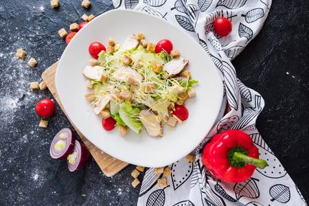 Fresh caesar salad with chicken on a white plate on dark stone background. Flat lay with ingridients for cook Stock Photo
