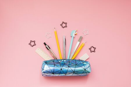 Back to school. Pencil case with school supplies on pink table.