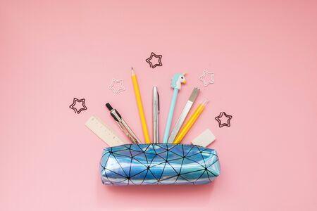 Zurück zur Schule. Federmäppchen mit Schulmaterial auf rosa Tisch.