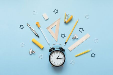 Alarm clock isolated on blue background. Wake-up time. Back to school flat lay.