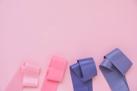 Fitness elastic band, elastic extenders of different colors for sports, on pink background. Fitness trend
