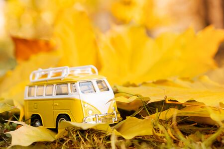 Autumn retro yellow van bus on autumn maple leaf background. Funny retro toy car with surfboard. Autumn travel and vacation concept.