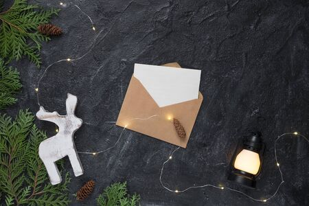 Christmas composition. Gifts, envelope, fir tree branches, white decorations on black background.
