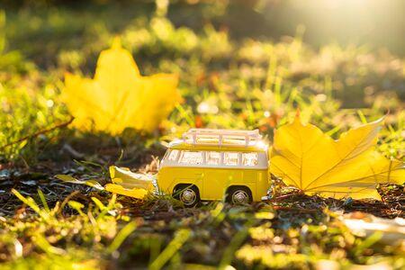 Autumn retro yellow van bus on autumn maple leaf background. Funny retro toy car. Autumn travel and vacation concept. 版權商用圖片