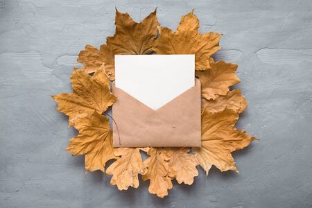 Autumn composition. Craft envelope. card mockup with autumn marple leaves on gray background. Flat lay, top view, copy space