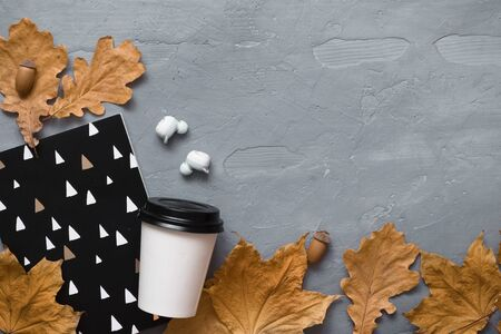 Autumn mood. Takeaway coffee, notebook, headphones with autumn leaves