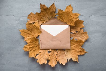 Autumn composition. Craft envelope. card mockup with autumn marple leaves. Flat lay, top view, copy space