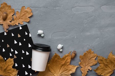 Autumn composition. Takeaway coffee, notebook, headphones with autumn leaves. Flat lay, top view, copy space