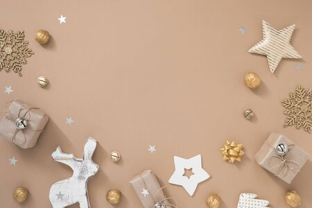 Christmas composition. Frame with gifts, craft and golden decorations on pastel beige background.