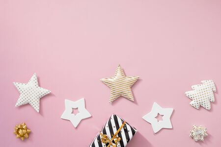 Christmas composition. Christmas gifts, black and golden decorations on pastel pink background.