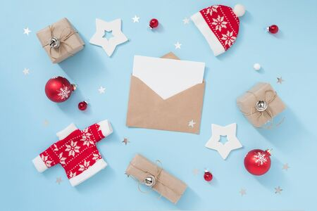 Christmas or winter composition with envelope and red decorations on pastel blue background. New year concept. 版權商用圖片