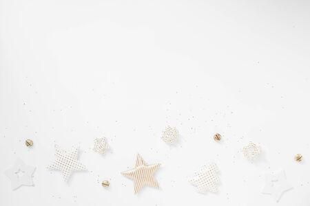 Christmas border. Golden stars, bells and bows on white background. Flat lay, top view, copy space