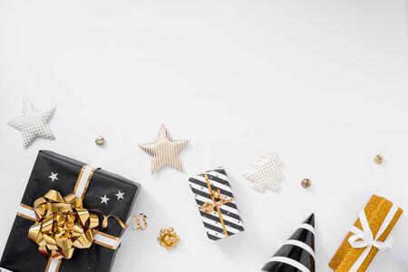 Stylish christmas decoration. Gifts, hats, black and golden decorations on white background 版權商用圖片