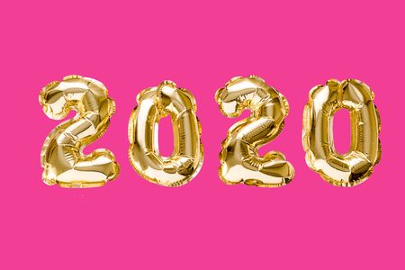Happy New year 2020 celebration. Gold foil balloons numeral 2020 on pink background