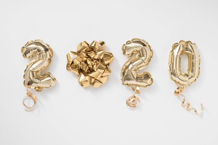 Happy New year 2020 celebration. Gold foil balloons numeral 2020 on white background