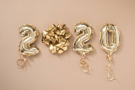 Happy New year 2020 celebration. Gold foil balloons numeral 2020 isolated on pastel beige background