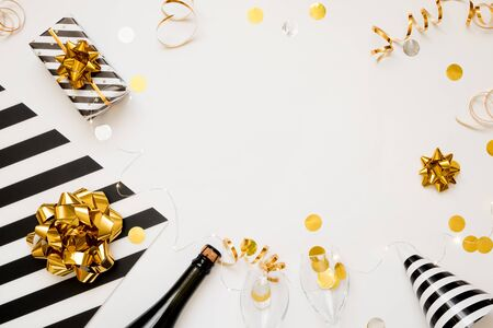 Christmas party composition. Gifts, hats, black and gold decorations on white background. Flat lay, copy space 版權商用圖片