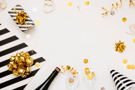 Christmas party composition. Gifts, hats, champagne bottle black and gold decorations on white background.
