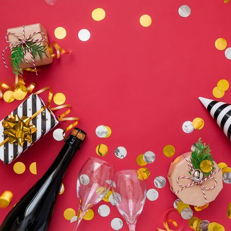 Christmas party composition. Gifts, hats, champagne bottle black and gold decorations on red background. 版權商用圖片