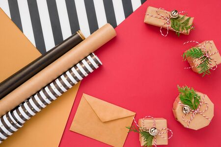 Christmas gift or present box wrapped in kraft paper with decoration on red background from above. Flat lay style.