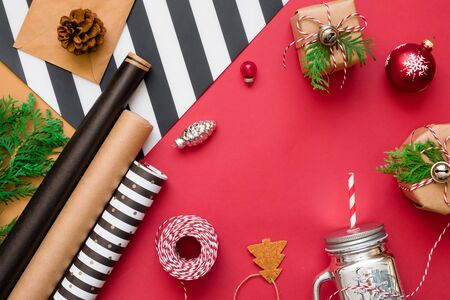 Christmas background with gift boxes, rope, papers rools and decorations on red. Preparation for holidays
