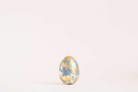 Easter golden decorated egg with golden potal isolated on white background. Minimal easter concept. Happy Easter card with copy space for text Top view, flatlay. Stok Fotoğraf