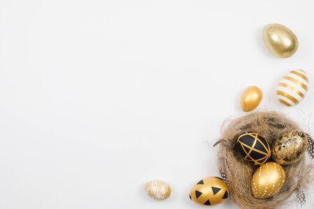 Easter golden decorated eggs in nest isolated on white background for web banner. Minimal easter concept. Happy Easter card with copy space for text. Top view, flatlay.