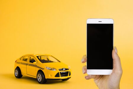 Urban taxi mobile online application concept. Toy yellow taxi car model. Hand holding smart phone with taxi service app on display. Mock up with copy space.