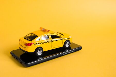 Urban taxi mobile online application concept. Toy yellow taxi car model. Hand holding smart phone with taxi service app on display. Mock up with copy space Stockfoto - 144806717
