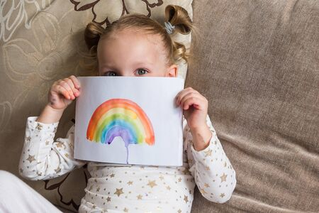 Kid painting rainbow during Covid-19 quarantine at home. Girl holding adrawing with rainbow. Stay at home Social media campaign for coronavirus, lets all be well, hope during pandemic