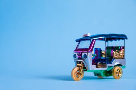 Model Toy tuk tuk isolated on blue background. Thai traditional taxi in Bangkok Thailand. Souvenir.