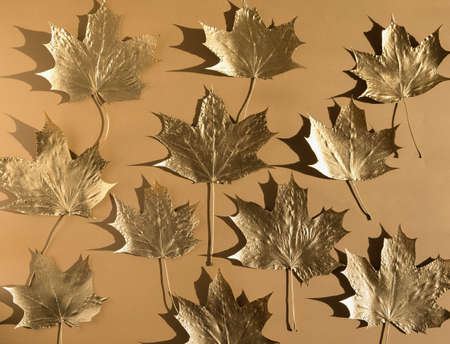 Autumn composition. Pattern made of autumn golden marple leaves on nude color background. Flat lay, top view, copy space
