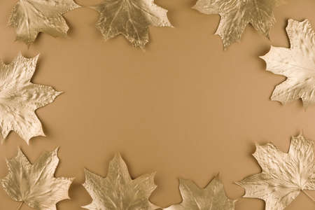 Autumn composition. Frame made of autumn golden maple leaves on nude background. Flat lay, top view, copy space