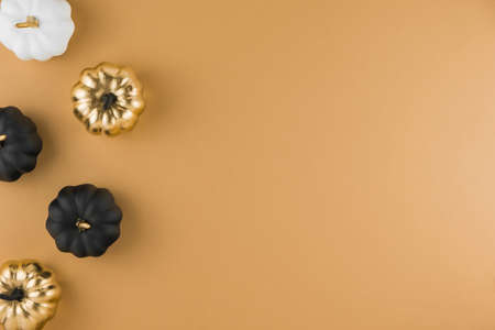 Autumn composition with decorative golden, white and black pumpkins on nude background. Flat lay, top view, copy space