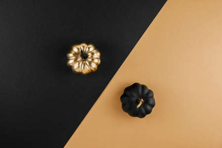 Seasonal fall sale, Black Friday. Discount minimal concept. Autumn composition with golden and black decorative pumpkins on nude background. Flat lay, top view, copy space. 版權商用圖片