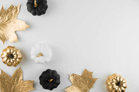 Autumn composition. Frame made of autumn golden leaves and decorative pumpkins on white background. Flat lay, top view, copy space