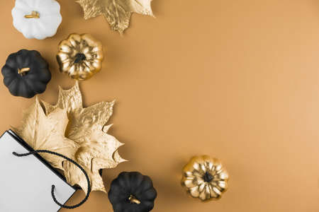 Autumn composition with golden maple leaves, decorative pumpkins and shopping bag on nude background. Seasonal fall sale, Black Friday. Flat lay, top view, copy space. 版權商用圖片