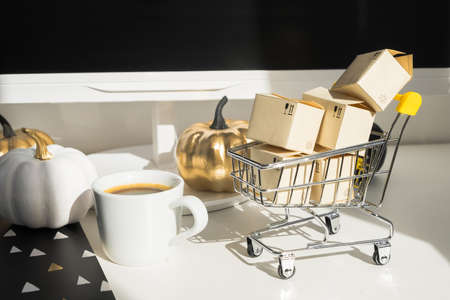 Workplace mock up concept. Modern home decor desktop computer with autumn decorations. Paper boxes in a trolley on the desktop. Online shopping concept 版權商用圖片