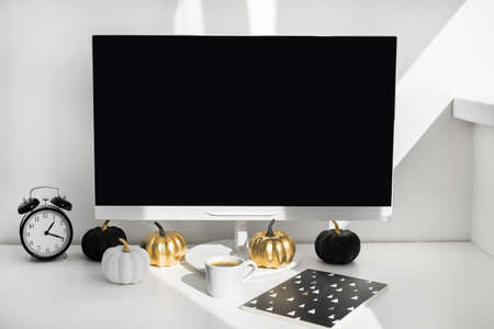 Blank screen desktop computer in modern minimal office room with autumn decorations. Paper boxes in a trolley on desktop. Online shopping concept