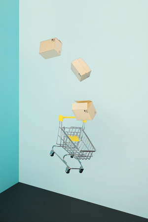 Levitating shopping cart and paper boxes on blue background. Safe online shopping on quarantine concept. Flying Empty supermarket shopping trolley with copy space