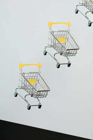 Levitating shopping carts on blue background. Safe online shopping on quarantine concept. Flying Empty supermarket shopping trolleys with copy space