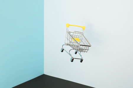 Levitating shopping cart on blue background. Safe online shopping on quarantine concept. Flying Empty supermarket shopping trolley with copy space