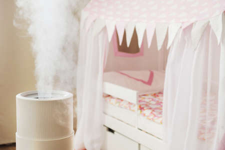 Modern air humidifier in childrens room, aroma oil diffuser at home. Improving the comfort of living in a house, Improving the well-being. Baby care