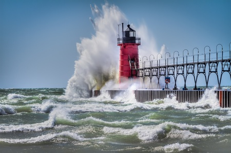 lake michigan lighthouse: En South Haven, Michigan, el faro es golpeado por las olas durante una tormenta de viento