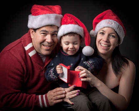Couple holding their son at christmas photo