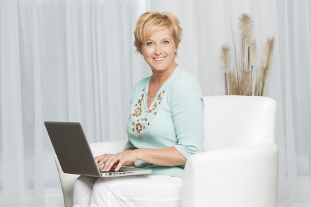 Portrait of a happy woman sitting on sofa using laptop and looking to camera Stock Photo - 19808682
