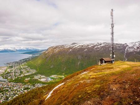 トロムソ、ノルウェーの周辺の山々 の上に電波塔 写真素材