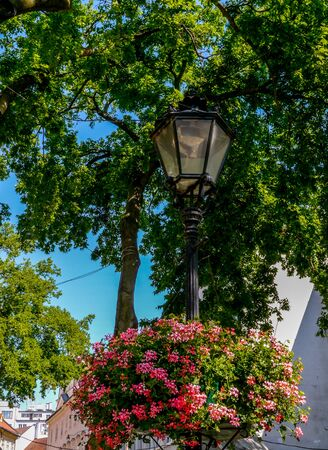 Colorful planters on traditional Central European street lamp