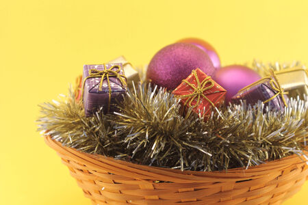 purples: Christmas basket with boxes of gifts, purples baubles and golden garlands Stock Photo