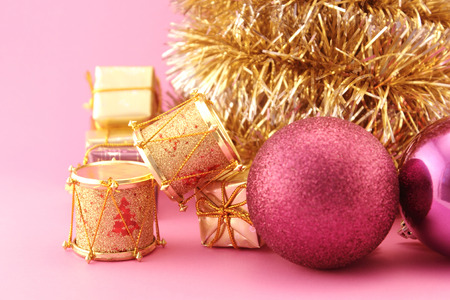 purples: Conceptual image about Christmas. Christmas decoration with golden drums, gifts, garlands and purples baubles.